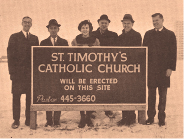 "Six People holding a sign saying ""St Timothy's Catholic Church will be erected in this site.""  The sign included the Pastors telephone number."